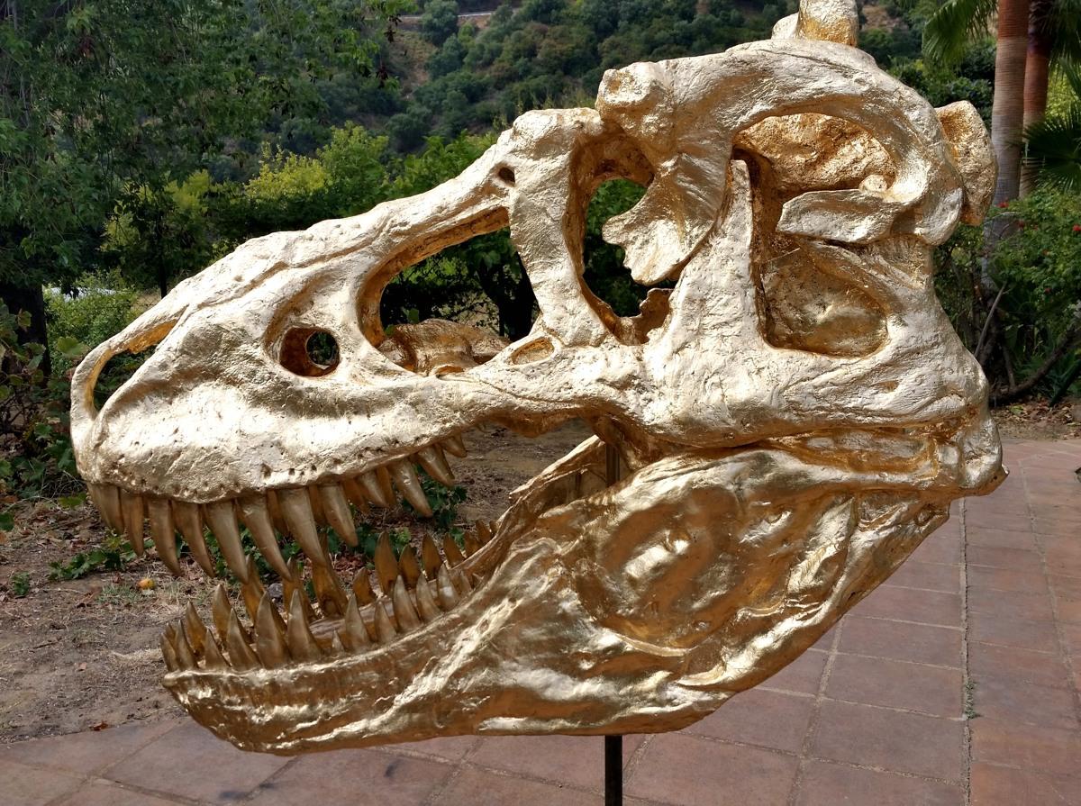 Réplica artística en oro de un Tiranosaurio.